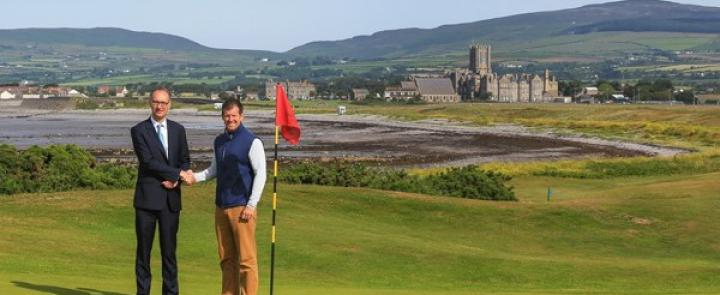 HM of King William's College Joss Buchanan & Golf Pro Dave Adams on the Links with the English boarding school in the background | Dickinson School Consulting